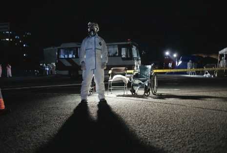 At a decontamination center, a fireman awaits arrivals from the potential contamination zone around the nuclear reactors at the Fukushima Daiichi power plant. The prospect of radiation introduced a threat all its own, and one throbbing with history. Photograph by Adam Dean.