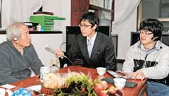 峯岸さん(左)に話を聞く中央大放送研究会の加藤さん(右)ら=東京都多摩市で